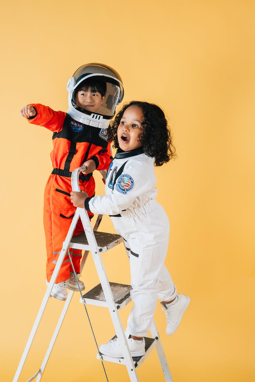 positive diverse children in astronaut costumes in studio